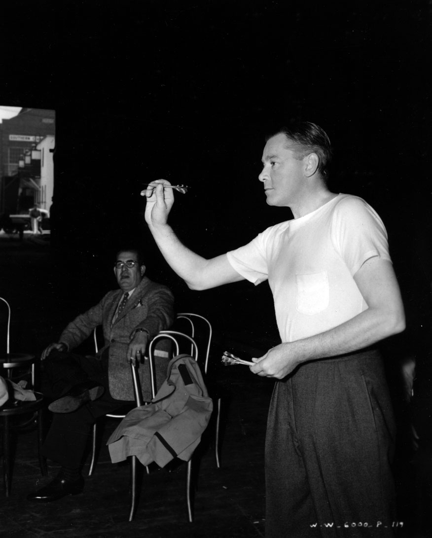 Herbert Marshall plays darts on set.