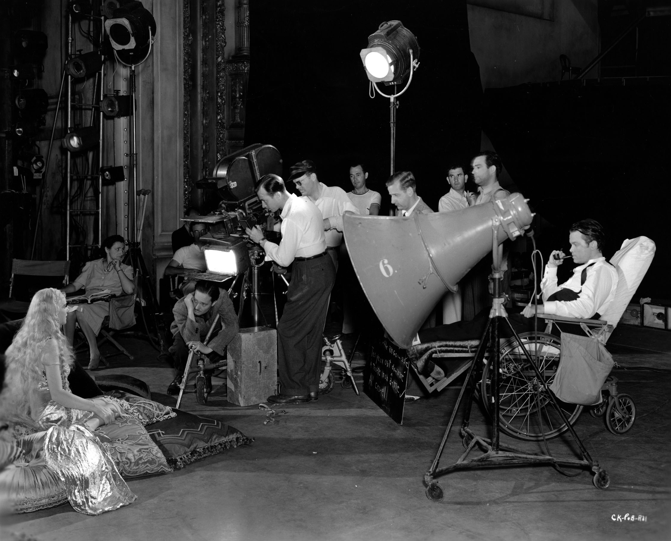 "Production still. Original caption reads: ""ORSON FILMS AN OPERA.  Directing from a wheelchair while an injured ankle heals, Orson Welles, right, is shown here overseeing rehearsals of an opera scene for his initial RKO Radio production, ""Citizen Kane.""  Welles plays the title role in the picture, also produces and directs.  Seated left is Dorothy Comingore, the young 'unknown' Welles chose for a leading role in the film.  Crouched before the camera is Gregg Toland, director of photography, while the balance"
