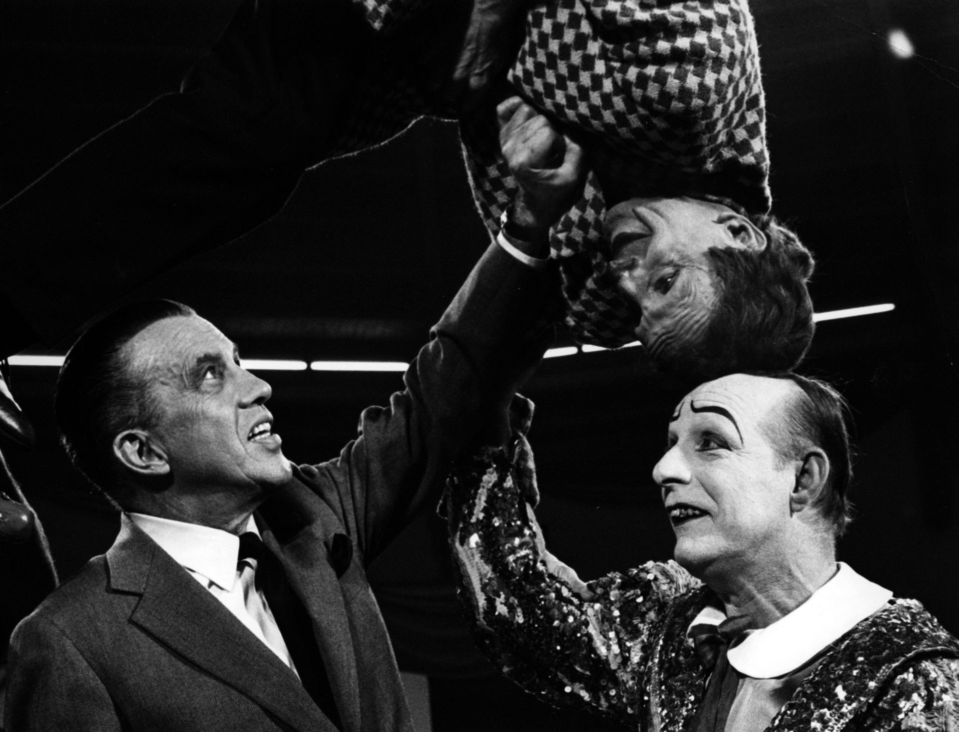 "Production still, circa 1965. Original caption reads, ""CLOWNING AROUND—Ed Sullivan joins the Rivels, Spanish clown act, who are among the outstanding circus stars on ""The Ed Sullivan Show"" Sunday, Dec. 19 (8:00-9:00 PM, EST) on the CBS Television Network.  The entire program, taped in color in Munich, is devoted to acts from major European circuses."""