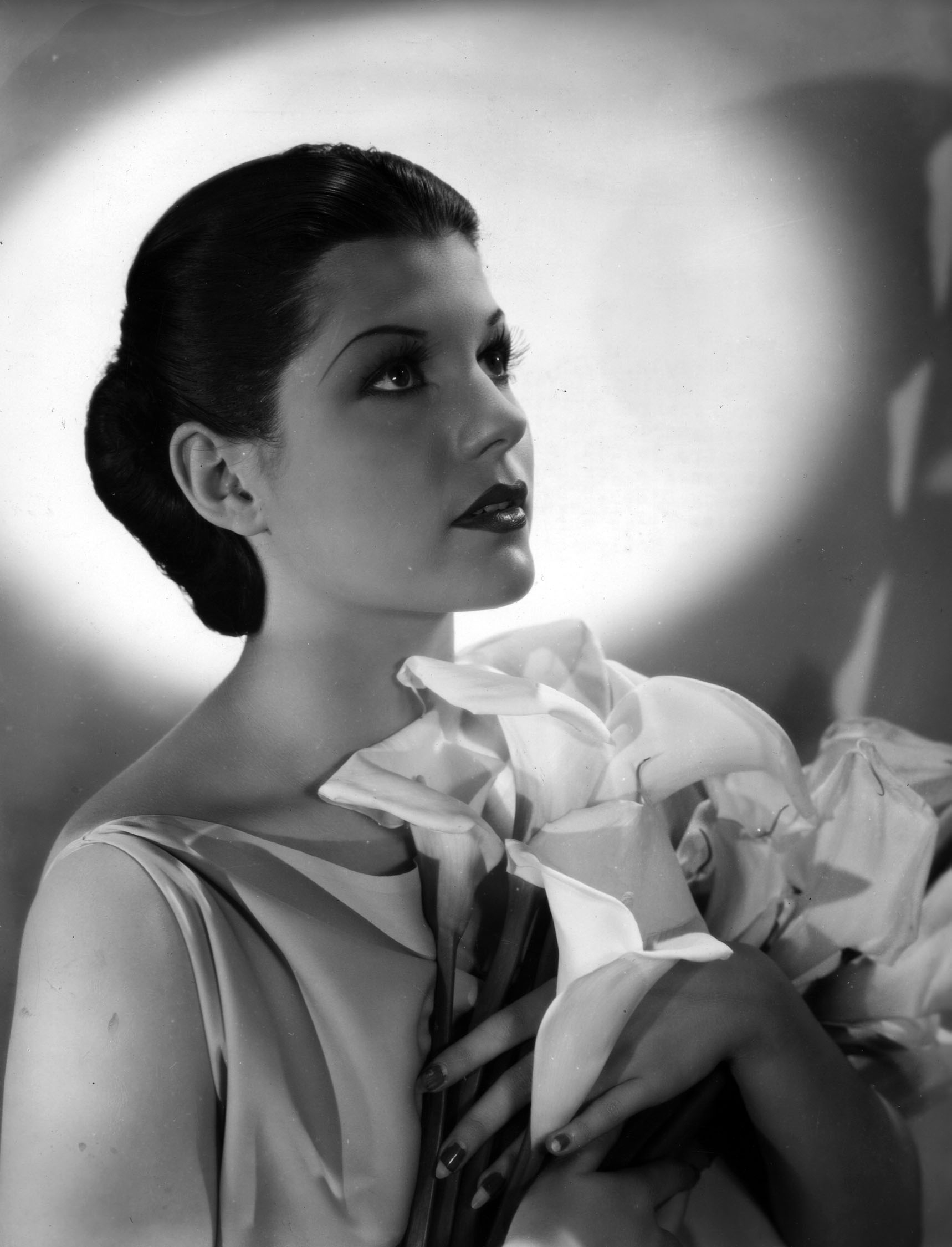 """Fox publicity still of Rita Cansino, circa 1936.  Original caption reads: """"EASTER MADONNA—Rita Cansino, beautiful Spanish-Irish actress, whose vivid dancing is a feature of 20th Century-Fox's 'Human Cargo', prepares  for the Easter Sunrise services which she attends regularly at the Hollywood Bowl."""""""