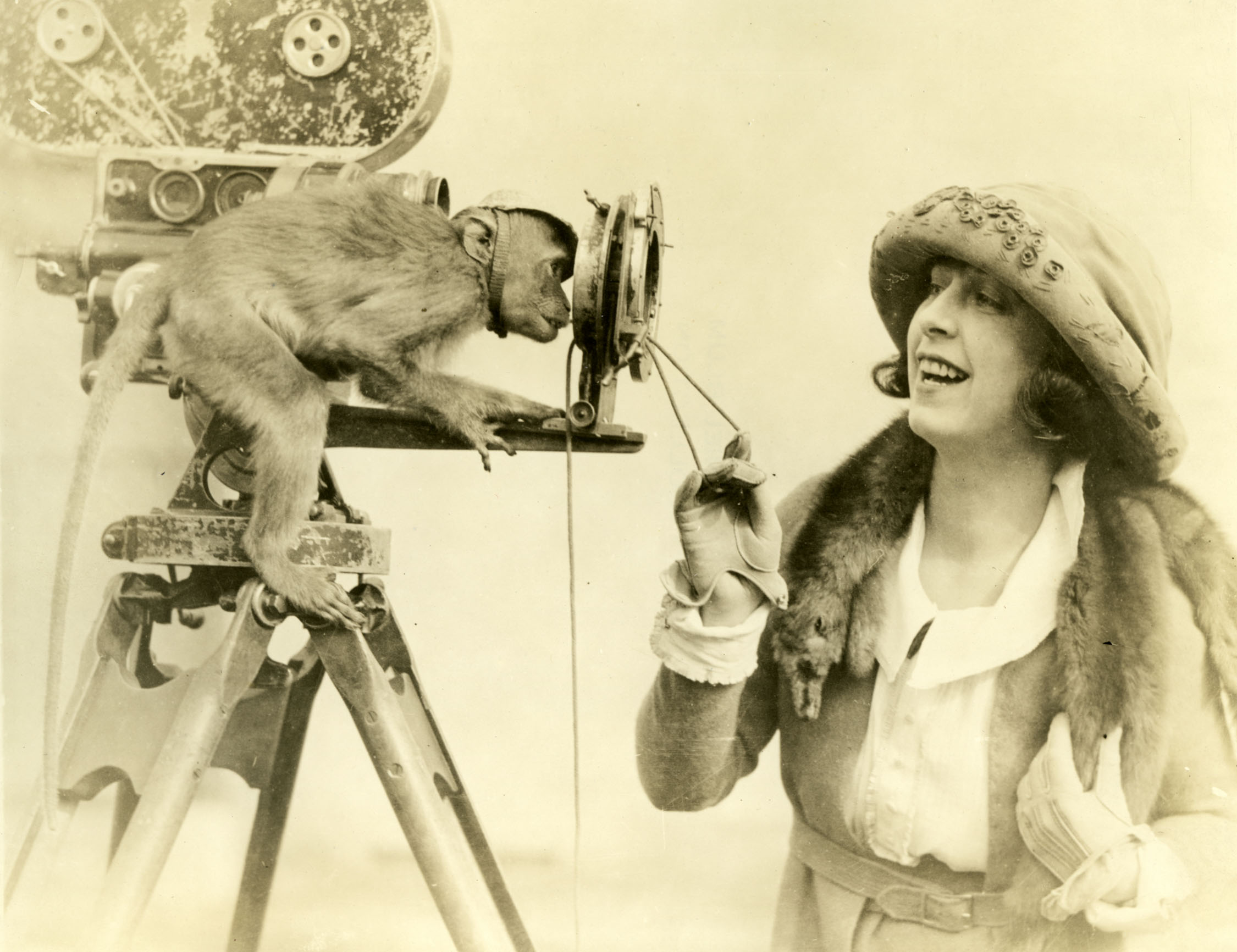 """Silent cinema star Dorothy Phillips and her pet monkey, circa 1918.  Original caption reads, """"This is one of the rare snapshots which a photographer gets only once in a peagreen moon. Dorothy Phillips, star of Allen Holubar's """"The Soul Seeker"""" is showing simian how a fade out is made with the frontal attachment to the camera. The monk is taking a canny amused interest in the prodeeding (sic)."""" (Holubar's film was released under the title A Soul for Sale.)"""