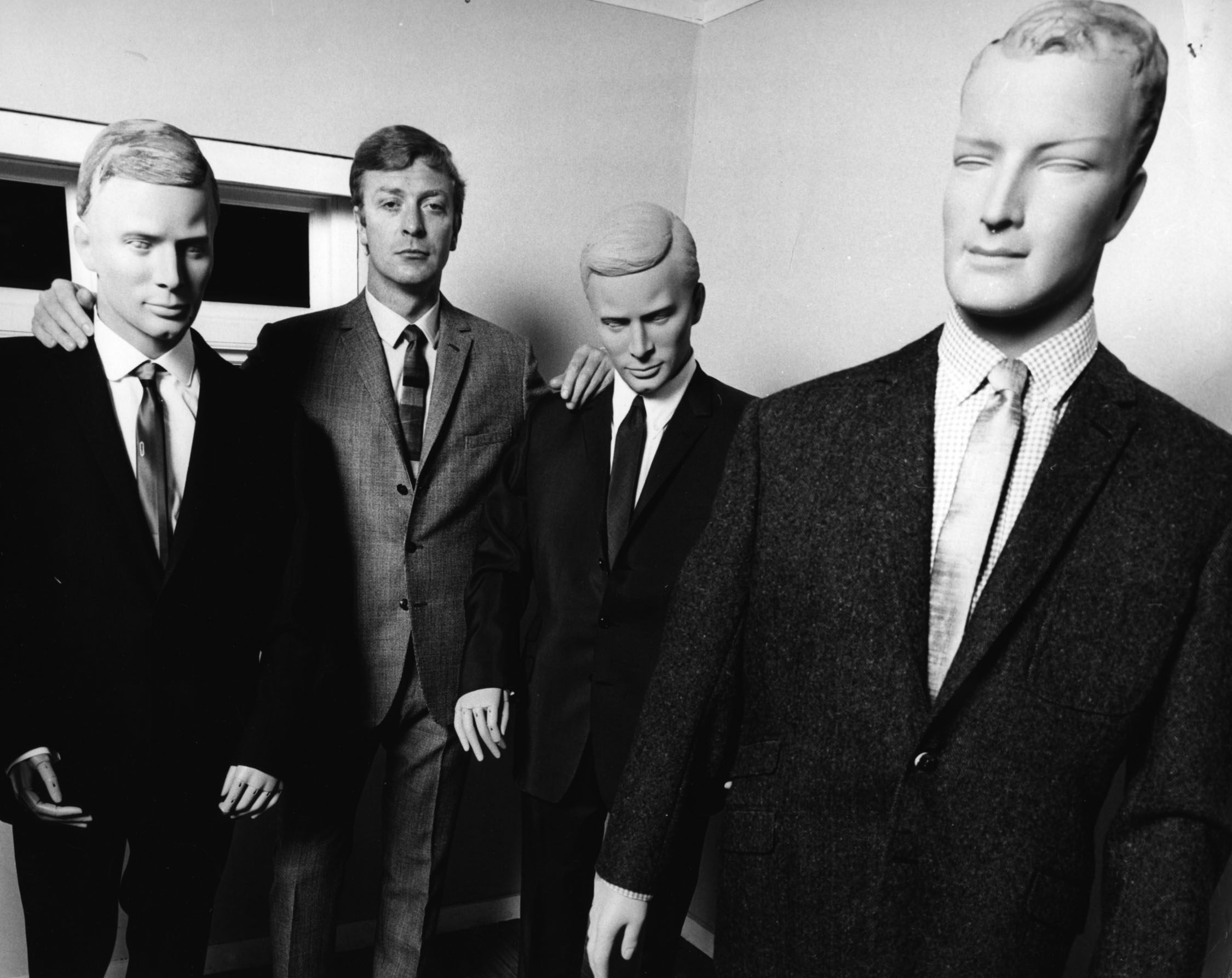 Michael Caine, star of Alfie (1966), poses with suits made to promote the film.