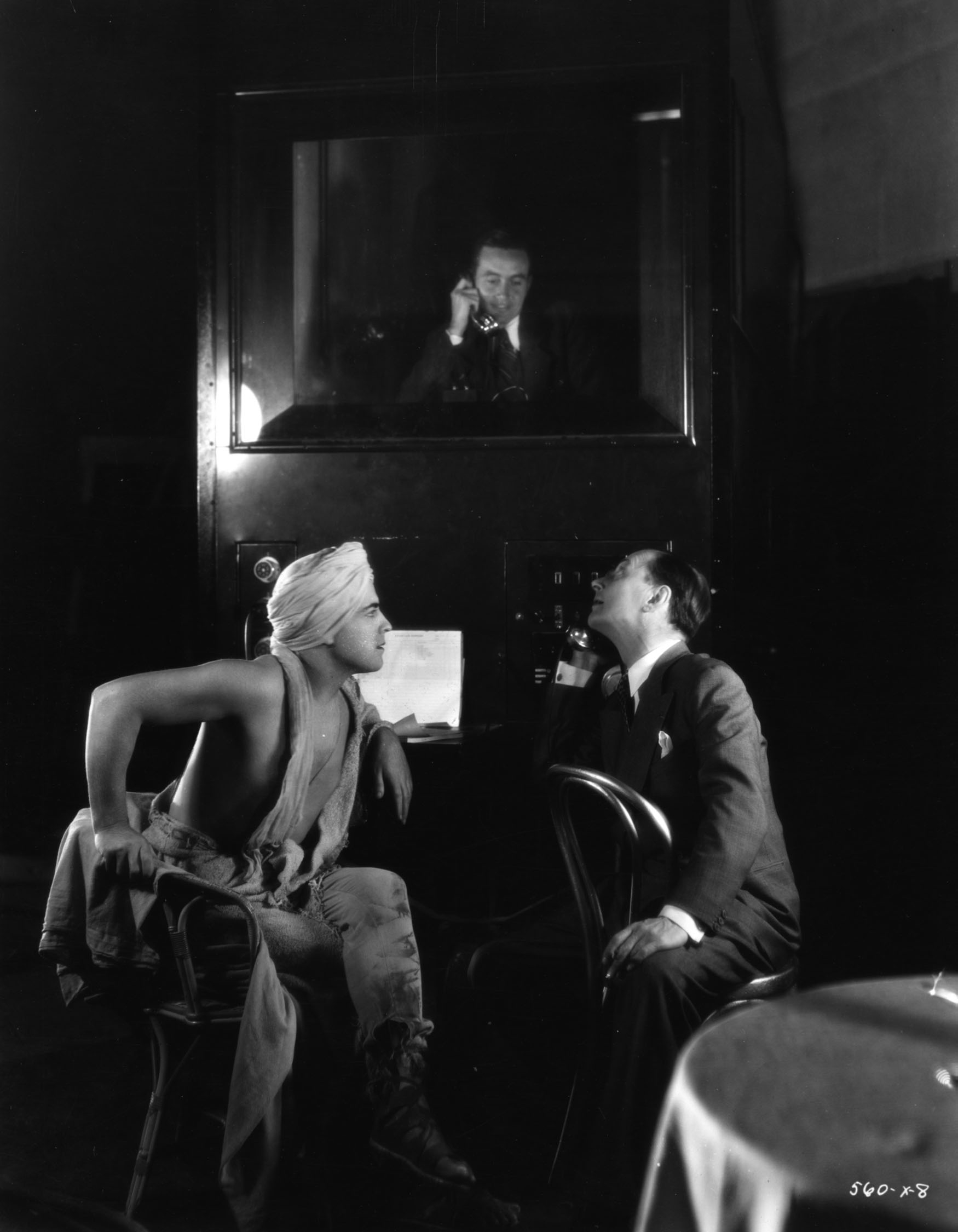 """Director Jacques Feyder and star Ramon Novarro on the set of the 1931 early sound feature Son of India (originally titled """"Son of Rajah"""").  Original caption reads, """"From his sound proof portable booth, via a horn on top of  it, the 'mixer' tells star Ramon Novarro and director Jacques Feyder what he thought of the quality of dialogue in the previous scene of Novarro's new M-G-M picture, 'Son of Rajah.'"""""""