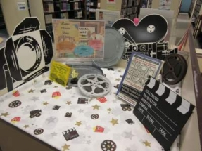 Home Movie Day Welcome Table with cutouts of a clapper, studio light fixture, and film camera.