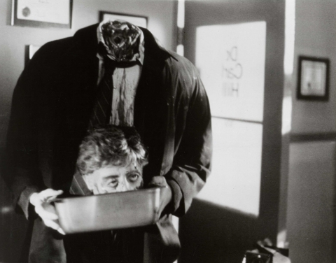 Film still from Re-Animator. A headless animated corpse carries its head in a metal bin.